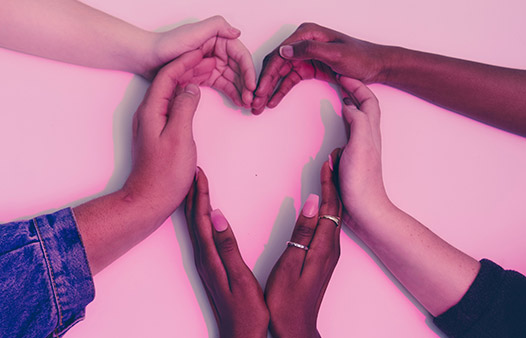 six hands of different colour come together to form a heart