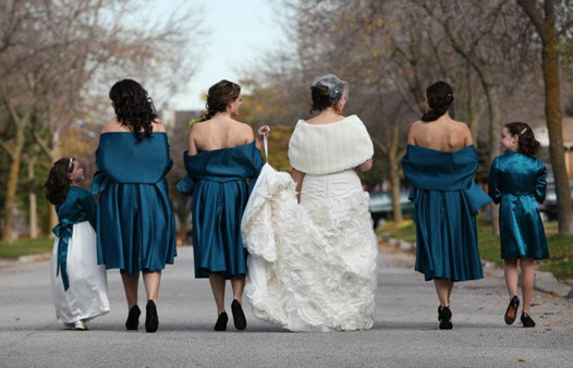 a bride and her wedding party face away from the camera and walk down a road
